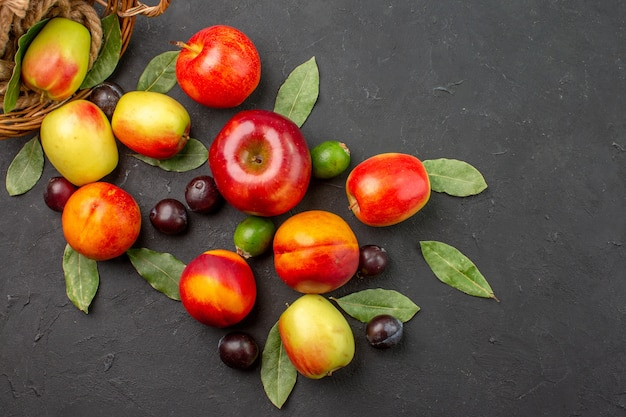 어두운 탁자에 있는 잘 익은 주스 나무에 자두와 복숭아를 넣은 신선한 사과