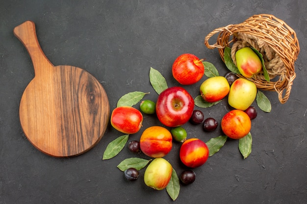 어두운 탁자에 있는 자두와 복숭아를 곁들인 신선한 사과를 잘 익은 나무 부드러운 비타민