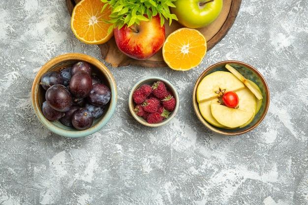 スライスしたオレンジとプラムと白い背景の上のビュー新鮮なリンゴ熟したまろやかなリンゴの果実新鮮