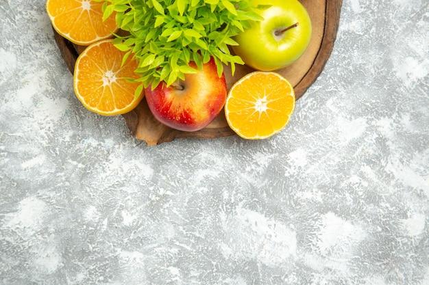 Вид сверху свежие яблоки с нарезанными апельсинами на светлом белом фоне спелые спелые яблочные фрукты свежие