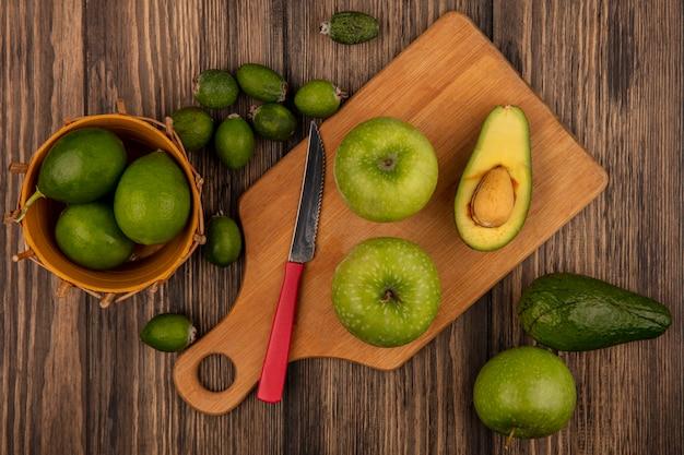 Vista dall'alto di mele fresche su una tavola da cucina in legno con coltello con limette su un secchio con feijoas e avocado isolato su uno sfondo di legno