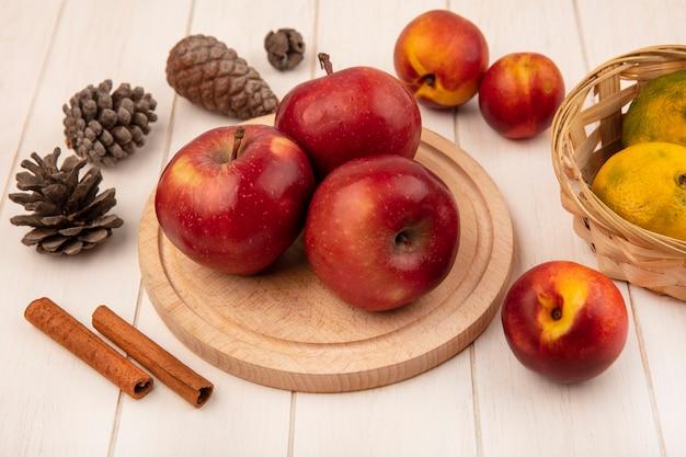 Vista dall'alto di mele fresche su una tavola da cucina in legno con mandarini su un secchio con pesche bastoncini di cannella e pigne isolate su una parete di legno bianca
