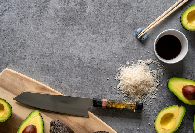 Top view of fresh avocados, a cutting board and knife, rice, and chopsticks on a grey surface