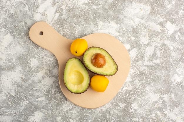Вид сверху свежие авокадо, полезные фрукты на белой поверхности