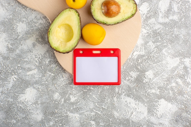 Top view fresh avocados useful fruits on white surface