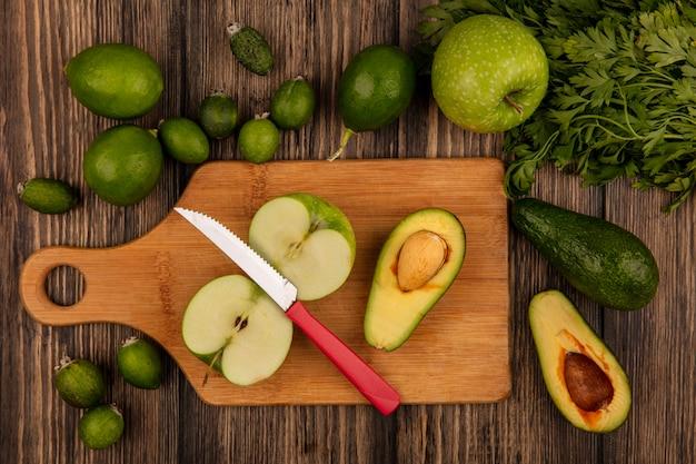 Vista dall'alto di avocado freschi con mele su una tavola da cucina in legno con coltello con lime feijoas e avocado isolato su una superficie in legno
