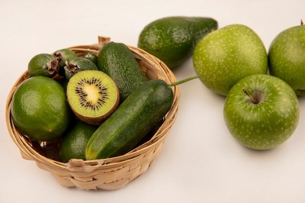 Vista dall'alto di avocado freschi con limette di cetriolo e feijoas su un secchio con mele verdi isolato su una superficie bianca