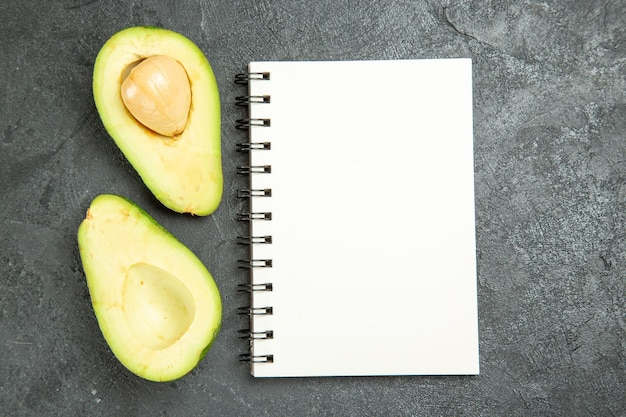 Top view of fresh avocados with notepad on grey surface