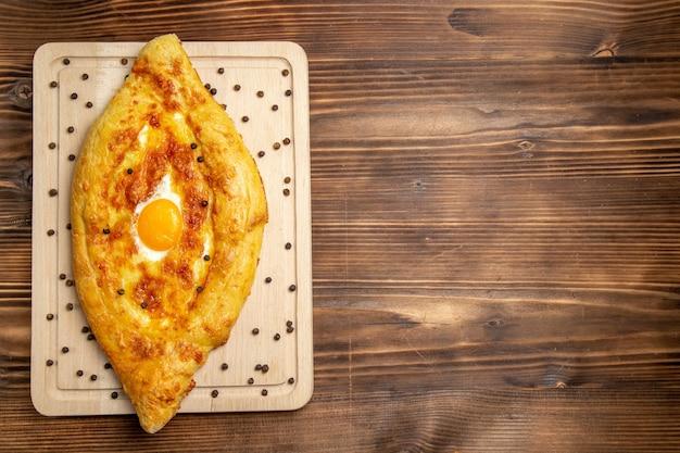 Vista dall'alto pane appena sfornato con uovo cotto su fondo rustico marrone pasta colazione uova panino cibo