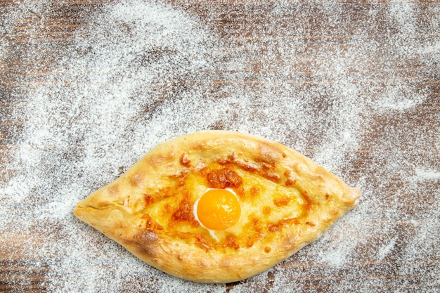 Vista dall'alto pane appena sfornato con uova cotte e farina sulla pasta di superficie marrone cuocere l'uovo del pasto del panino