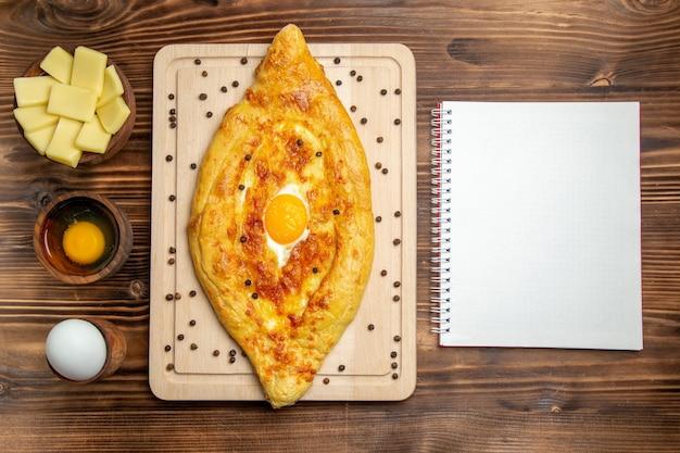 上面図茶色の机の上に調理された卵と焼きたてのパン生地食品朝食焼きパン食事卵