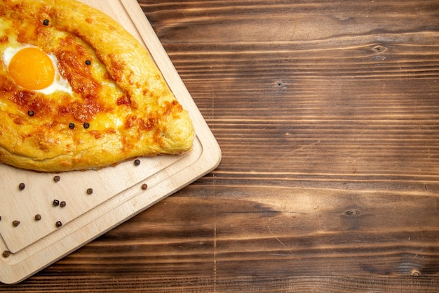 上面図茶色の木製の背景に調理された卵と焼きたてのパン生地朝食卵パン食品