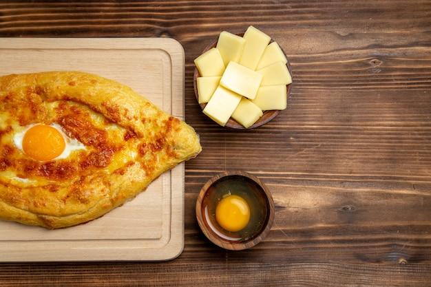 上面図茶色の木製デスクパン生地ミールパン朝食卵食品に調理された卵と焼きたてのパン