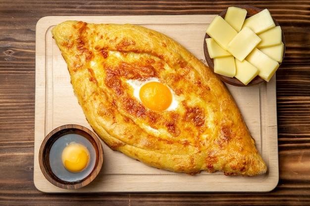 Вид сверху свежеиспеченного хлеба с вареным яйцом на коричневом деревянном полу, тесто, булочка, завтрак, яйца, еда