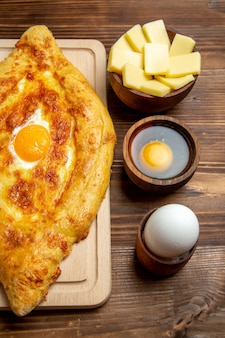 上面図茶色の木製の机の上に調理された卵と焼きたてのパン生地食事パン朝食卵食品