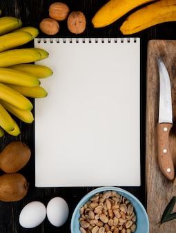 Vista dall'alto di banane fresche e kiwi con sketchbook, noci e arachidi e coltello da cucina su una tavola di legno su nero