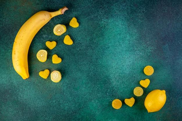 Vista superiore della banana e del limone freschi con le caramelle della marmellata d'arance su verde scuro con lo spazio della copia