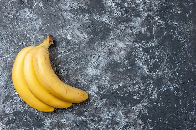 Top view fresh bananas on grey background free space