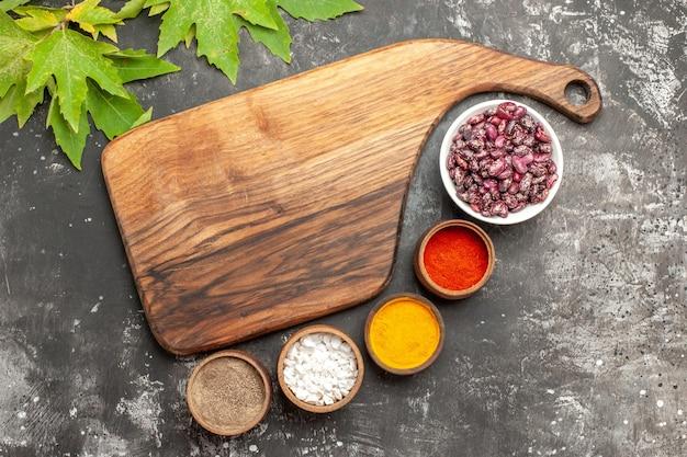 暗い表面にさまざまな調味料を入れた新鮮な豆の上面図