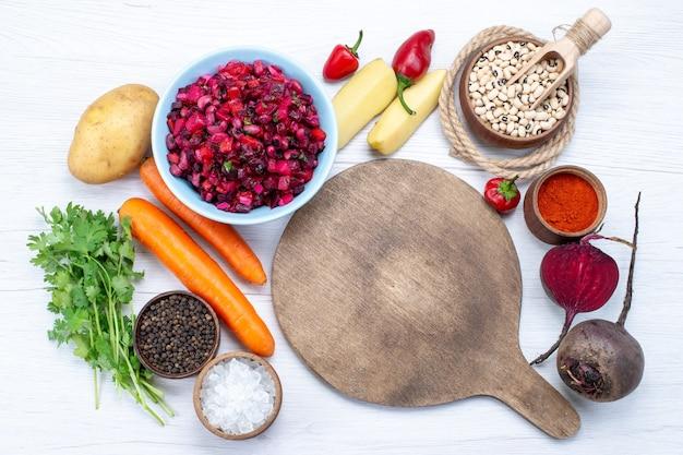 Vista dall'alto di insalata di barbabietole fresche con verdure a fette insieme a fagioli crudi carote patate su bianco, insalata fresca di verdure pasto cibo