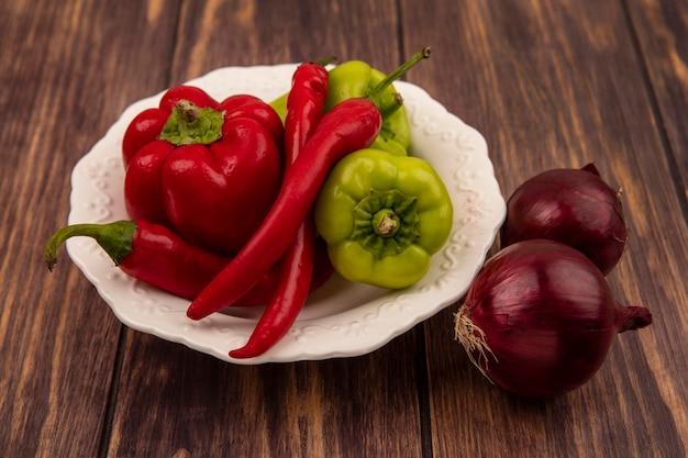 Vista dall'alto della campana fresca e peperoncino su una ciotola con cipolle rosse isolato su uno sfondo di legno