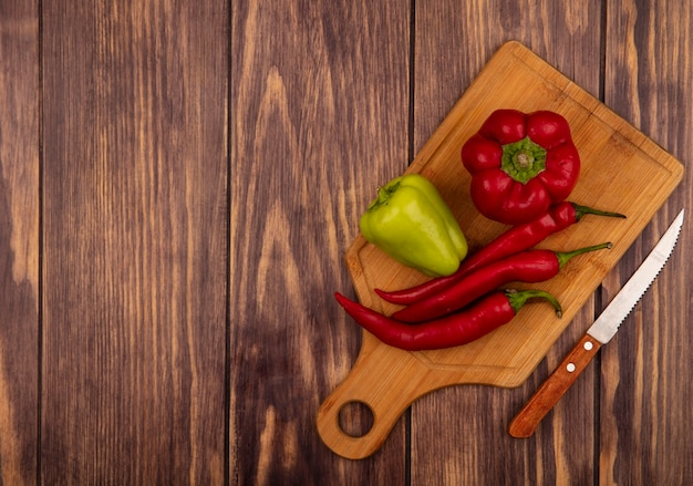 Top view of fresh bell and chili peppers on a wooden kitchen board with knife on a wooden wall with copy space