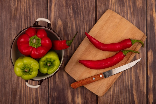Top view of fresh bell peppers on a bowl with chili peppers on a wooden kitchen board with knife on a wooden wall