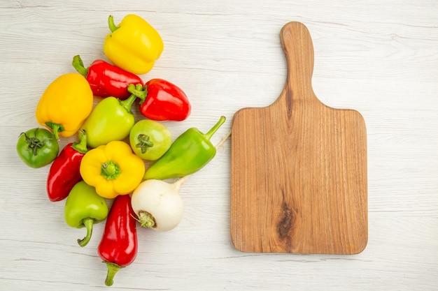 Вид сверху свежий сладкий перец разного цвета на белом фоне салат спелое фото цвет еды