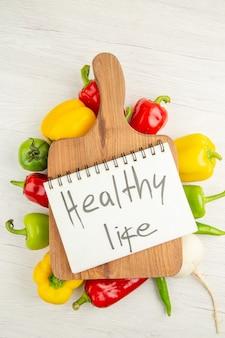 上面図新鮮なピーマン白い背景の上の茶色の木製の机で異なる色サラダダイエット熟したカラー写真健康的な生活