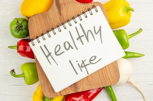 上面図新鮮なピーマン白い背景の上の茶色の木製の机で異なる色サラダダイエット熟した食事カラー写真健康的な生活