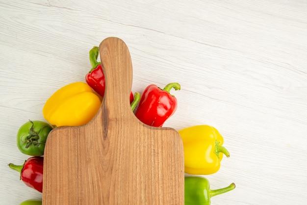 Вид сверху свежий сладкий перец разного цвета с коричневым деревянным столом на белом фоне салат, диета, спелая еда цветная фотография
