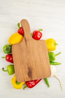 Вид сверху свежего болгарского перца разного цвета с коричневым деревянным столом на белом фоне салат спелое фото цвет еды
