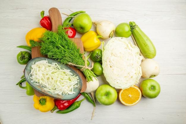 上面図白い背景にリンゴと緑の新鮮なピーマン熟した色のサラダ健康的な生活の食事