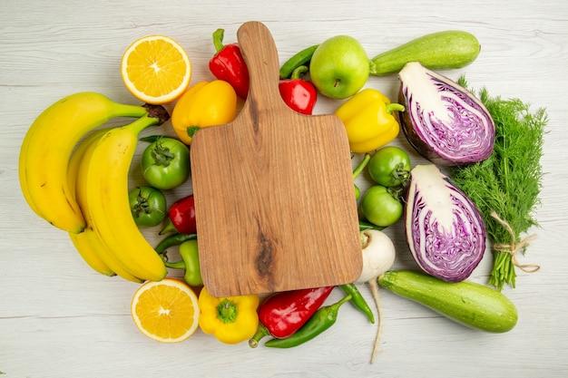 Vista dall'alto peperoni freschi con mele banane e cavolo rosso su sfondo bianco colore maturo dieta sana insalata