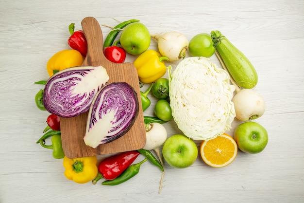 Vista dall'alto peperoni freschi con mele cavolo sullo sfondo bianco insalata di colori maturi dieta sana