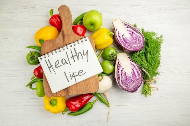 Vista dall'alto peperoni freschi con mele e cavolo rosso su sfondo bianco colore maturo dieta sana insalata