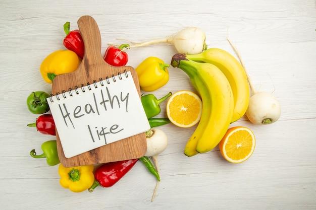 上面図新鮮なピーマンとバナナとオレンジの白い背景ダイエットサラダ健康的な生活写真熟した色