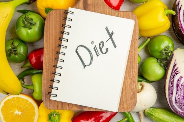 Вид сверху свежий сладкий перец с бананами и красной капустой на белом фоне цветной диета спелый салат для здорового образа жизни фото