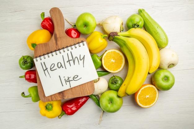 Вид сверху свежий сладкий перец с бананами, яблоками и апельсином на белом фоне салат здоровый образ жизни фото спелый цвет диета