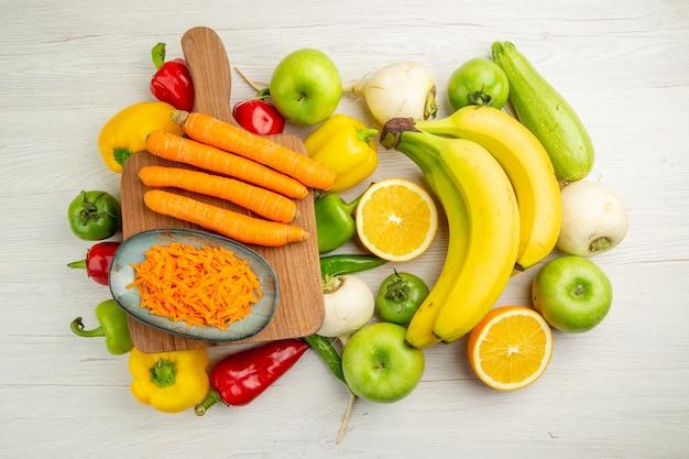 上面図新鮮なピーマンとバナナニンジンとリンゴの白い背景写真サラダ健康的な生活熟した色の食事療法