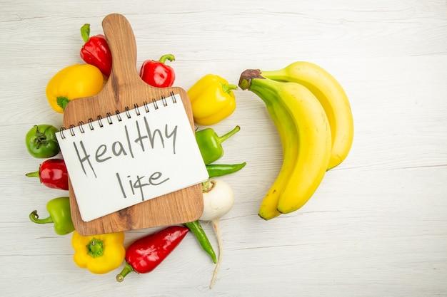 上面図白い背景の上のバナナと新鮮なピーマンダイエットサラダ健康的な生活熟した色