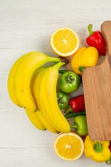 上面図白い背景にバナナと新鮮なピーマン熟した色健康的な生活ダイエットサラダ写真