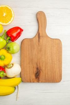 上面図白い背景にバナナと新鮮なピーマン熟した写真フルーツミールカラーサラダ熟した