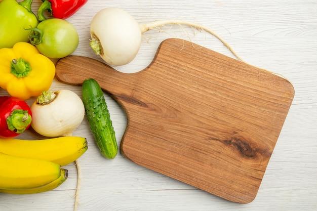 Vista dall'alto peperoni freschi con banane su sfondo bianco foto matura insalata di farina di frutta colore maturo