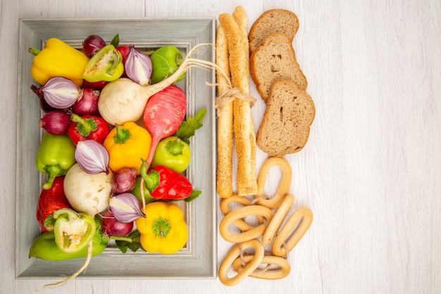 Vista dall'alto peperoni freschi con ravanello e pane sul tavolo bianco
