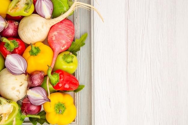 Vista dall'alto peperoni freschi con ravanello e cipolle sul tavolo bianco