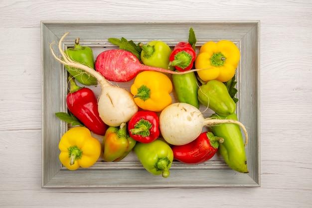 Vista dall'alto peperoni freschi con ravanello sul tavolo bianco