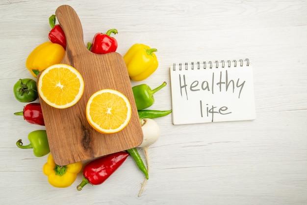 Вид сверху свежий сладкий перец с нарезанным апельсином на белом фоне цвет салата здоровый образ жизни диета фото спелые