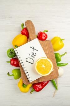 Vista dall'alto peperoni freschi con fette di arancia su sfondo bianco insalata colore maturo dieta sana foto