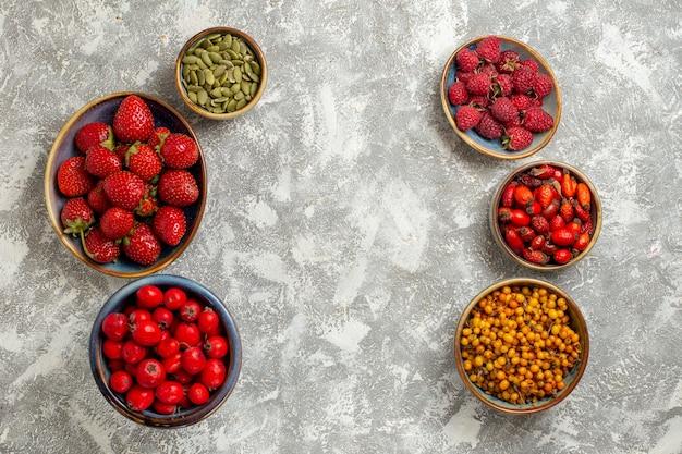 Vista dall'alto di frutti di bosco freschi frutti all'interno di piastre su sfondo bianco